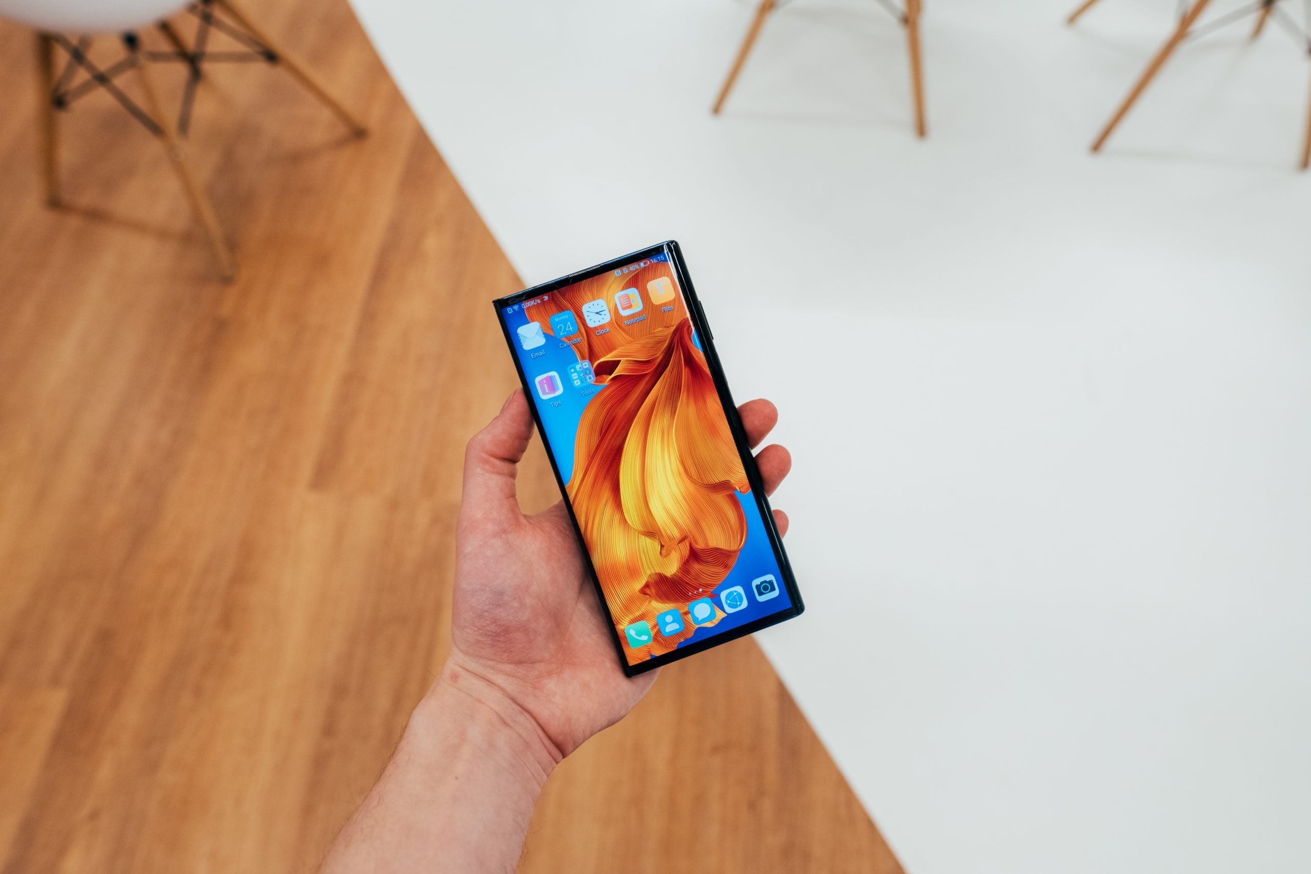 person holding blaHuawei Mate X Headck android smartphone
